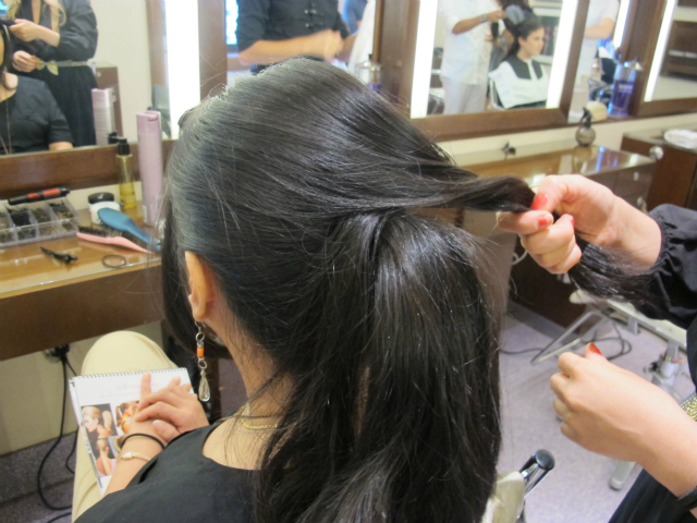 Pak begins wrapping front sections of hair around the ponytail.