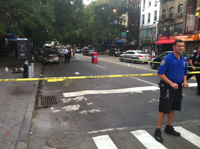 Police guard the scene where an officer shot a dog, East 14th Street and Second Avenue, on August 13, 2012, after it lunged at him, police said.
