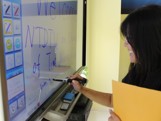 "A Time Warner Cable spokeswoman tests out the ""smart board"" at Good Shepherd Services' new computer learning lab."
