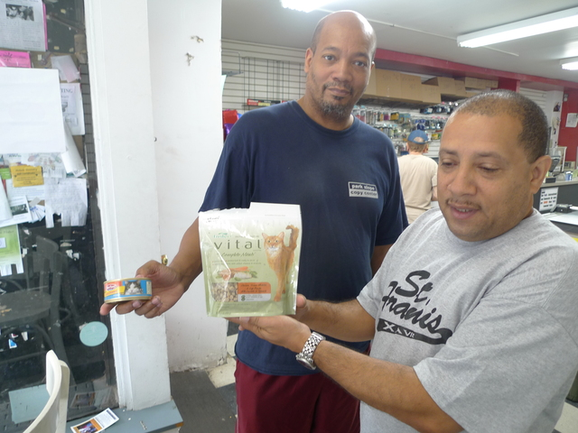 Park Slope Copy Center's Darius Sickles and Alfonso Maldonado with the special soft food they feed their store cats, who have bad teeth.