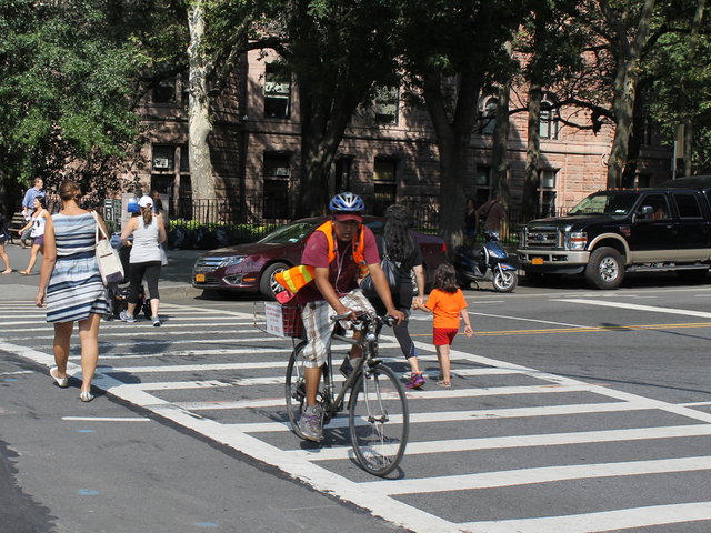 A food-delivery cyclist rides on Columbus Avenue on Aug. 16, 2012. The city will ramp up its enforcement of traffic rules for commercial cyclists in January.