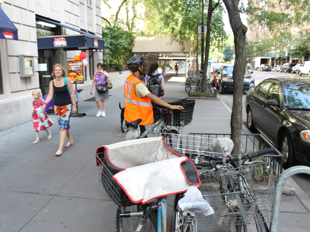 A food-delivery cyclist locks his bike outside the Upper West Side restaurant Dallas BBQ on Aug. 16, 2012. The city will ramp up its enforcement of traffic rules for commercial cyclists in January.