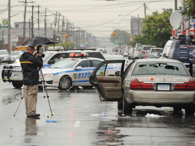 Crime scene officers take photos of the livery cab on Utica Avenue at Avenue M on Saturday Aug. 18, 2012.