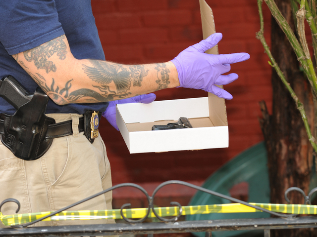 The gun allegedly used to shoot the livery cab passenger is collected by crime scene officers on Saturday, Aug. 18, 2012.