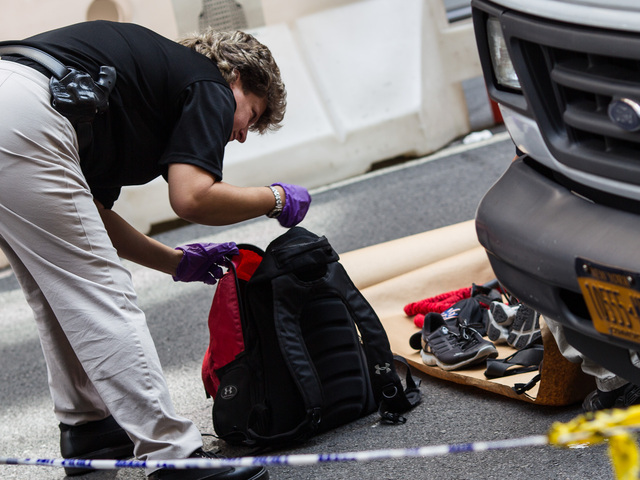 NYPC Crime Scene Officers inspect the contents of the victims bag outside the Empire State Building on 24th, 2012.