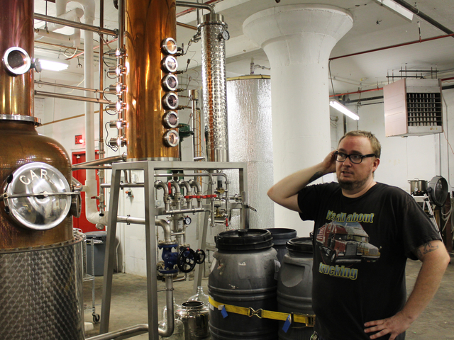Assistant distiller David Lewis stands in front of Van Brunt Stillhouse's handmade copper stills.