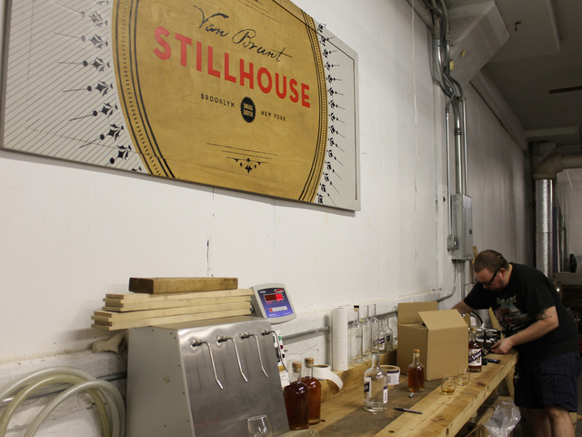 Assistant distiller David Lewis, 36, labels bottles on Due North rum at the Van Brunt Stillhouse. Owner Daric Schlesselman's wife, Sarah Ludington, painted the distillery's signs, Lewis said.