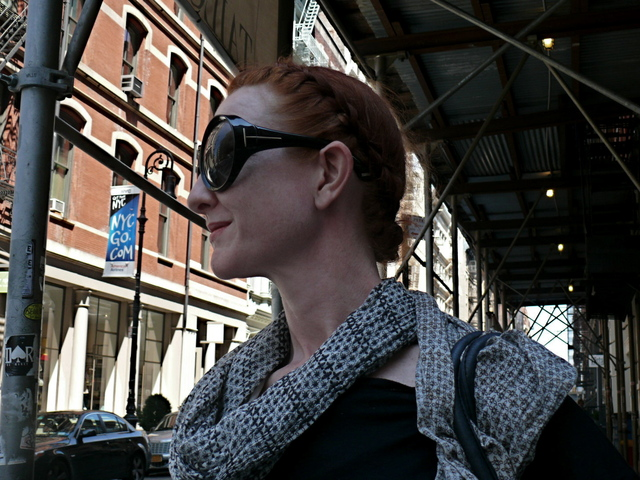 Braided hair, full-circle Tom Ford glasses and a light scarf in SoHo.