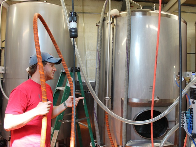 Brewer's assistant Simon Cox, 24, in red at left, prepares to pull yeast from one of Sixpoint Brewery's 465-gallon tanks.