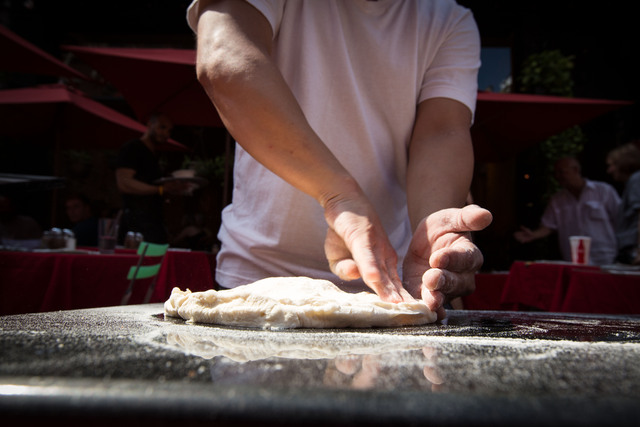 Hernandez prepares the flour for the pizza before tossing it on Mulberry Street September 1, 2012.