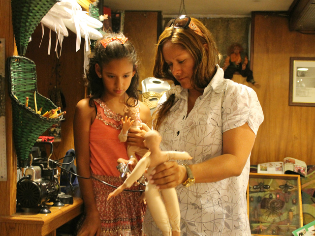 Vicky and Jackie Escalona practice airbrushing a doll.