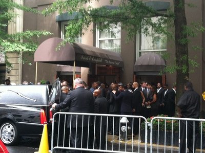Chris Lighty's casket was brought out to the hearse as a crowd on the sidewalk looks on.