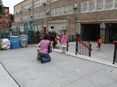 A student poses outside Park Slope's P.S. 321 on the first day of school in September 2012.