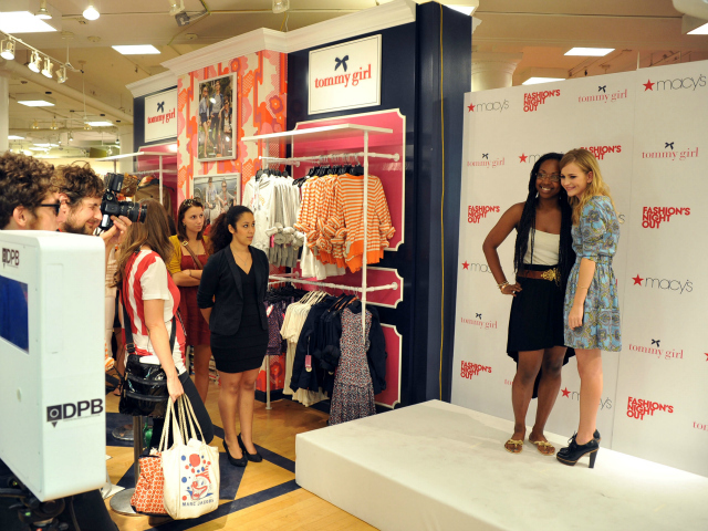 Actress Britt Robinson poses with a fan at Macy's for Fashion's Night Out, Sept. 6, 2012.