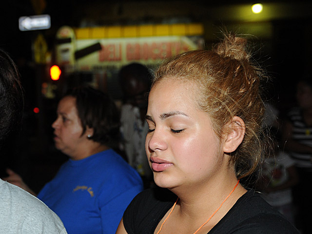 A young woman who said she was cousins with Reynaldo Cuevas protests and mourns his loss across the street from the bodega where he was killed, Sept. 7, 2012.