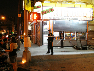 A police officer stands guard outside the bodega where Reynaldo Cuevas was killed.