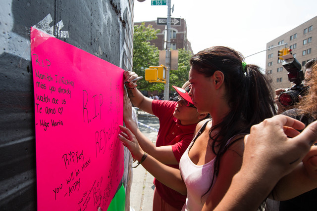 Friends hang posters to memorialize Reynaldo Cuevas, 20, after he was shot by a police officer outside the deli where he worked, September 7, 2012.
