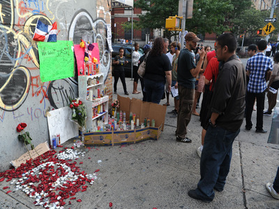 A vigil gathers the day after Reynaldo Cuevas was shot accidentally by a cop while fleeing an armed robbery at his bodega.