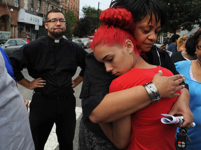 Carmen Berganzo is comforted by Rev. Que English during a vigil for Reynaldo Cuevas, as Rev. Ruben Austria looks on.