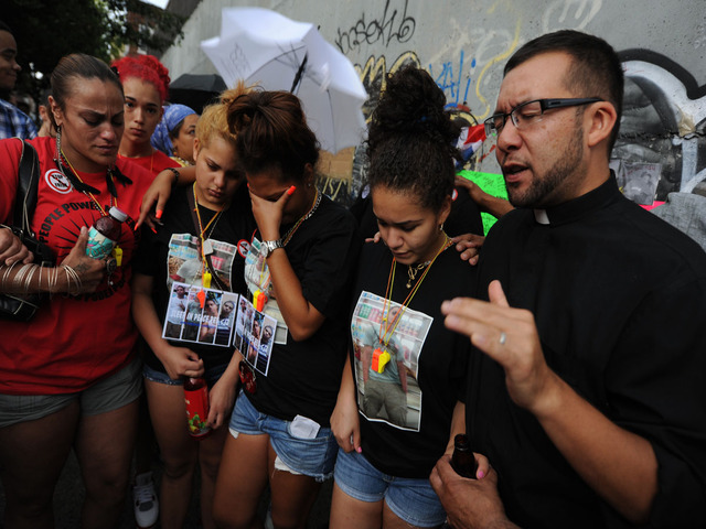 The Rev. Ruben Austria leads a brief prayer service during vigil.  From left in black shirts:  Reynaldo's cousin Massiel Cuevas, friend Gizelle Guzman and cousin Ashley Cuevas.