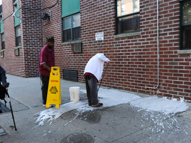 Maintenance workers wash away the blood outside of 660 Gates Avenue where a man was stabbed on Monday September 10th, 2012.