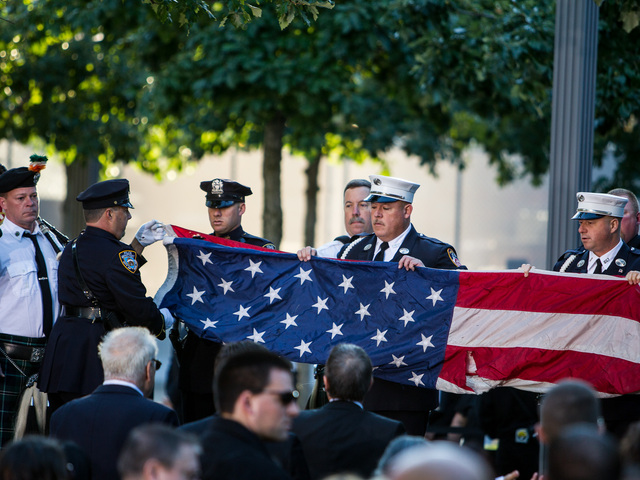 First responders folded a flag at the 9/11 Memorial Sept. 11, 2012.