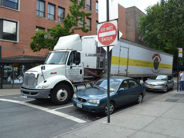 A truck parked in a turning lane on 75th Street.