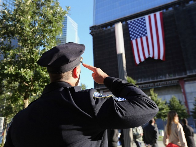 An NYPD officer saluted a flag on 1 World Trade Center at the anniversary ceremony Sept. 11, 2012.
