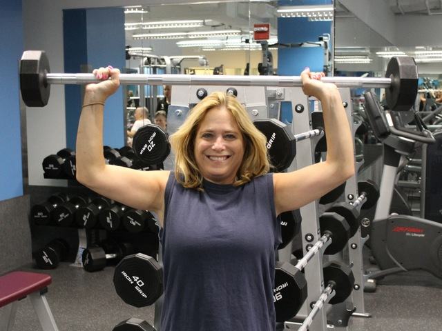 Amy Gould presses weight over her head at the McBurney YMCA's new strength training center.