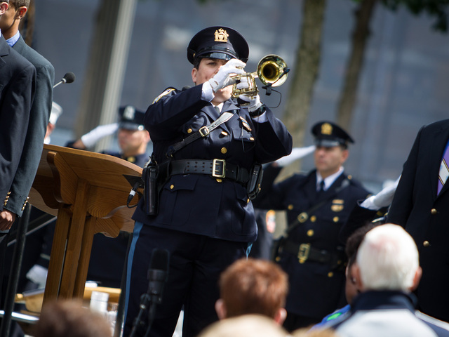 An NYPD officer plays the final salute at 1 World Trade Center on the anniversary ceremony Sept. 11, 2012.