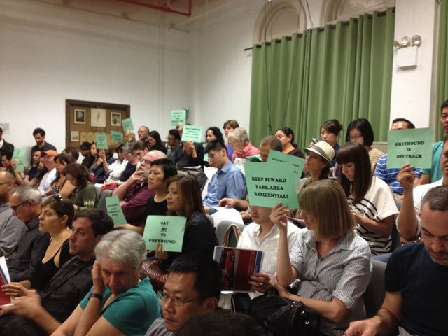 Local residents hold up signs to protest Greyhound's proposal to have a curbside bus stop on Essex Street.