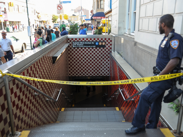 An Officer guards an entrance at the Jamaica Station where three people were stabbed on Wednesday September 12th, 2012.