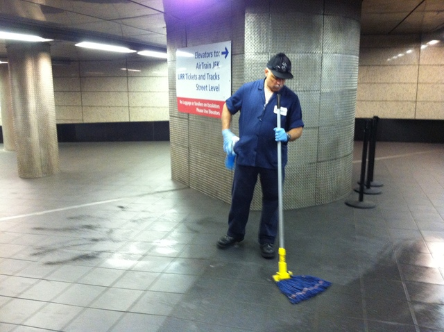 An employee at a Jamaica, Queens, train station cleans blood from the scene of a stabbing Wednesday, Sept. 12.