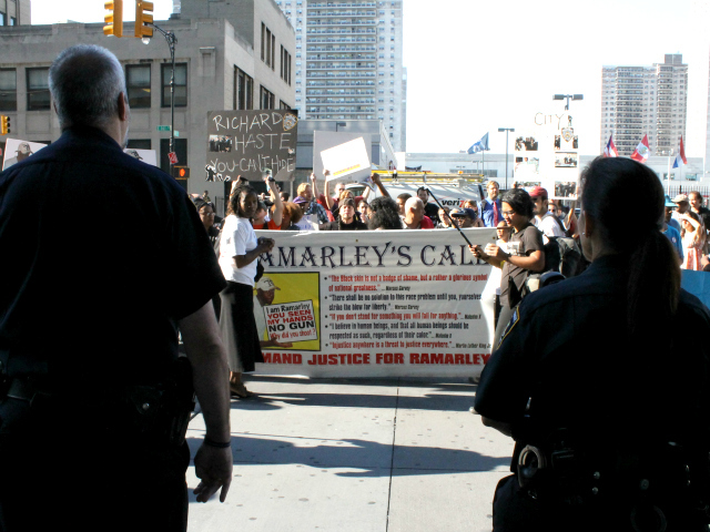 Court police officers watch a rally for Ramarley Graham outside the Bronx County Hall of Justice.