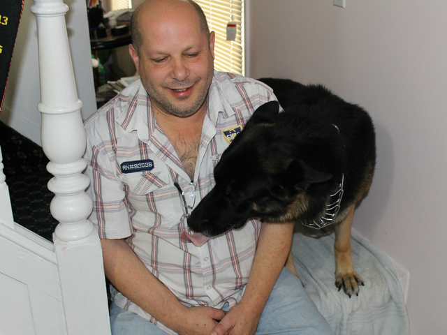 Joseph Butrico and his dog Maxwell inside their Marine Park Home. The city fined Butrico after neighbors complained about Max's excessive barking.