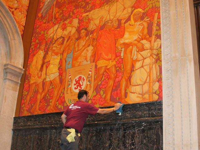 A man cleaning one of the Theodore Roosevelt murals.