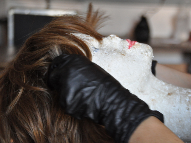 Sarah Nowicki fitted a wig on a mannequin's head to style it.