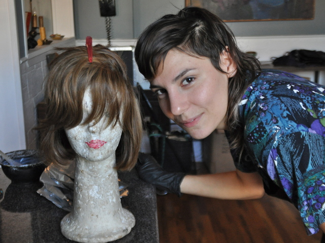 Sarah Nowicki posed in her kitchen with a wig she prepared to highlight for a Hasidic customer she's never met.
