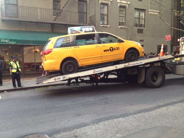 A tow truck removes the taxi involved in a fatal accident at East 69th Street and First Avenue on Sept. 17, 2012.