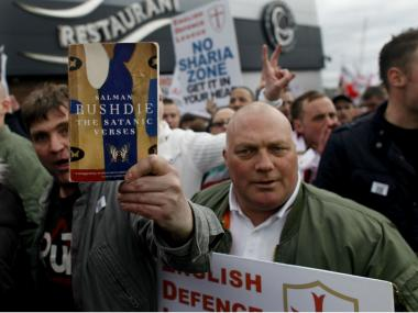 Members of the far-right English Defence League (EDL) brandish placards and Salman Rushdie's book 'The Satanic Verses' during an anti-Islam rally in Luton on May 5, 2012. The demonstration, dubbed by organisers 'Love Luton' celebrates three Years Of The English Defence League.