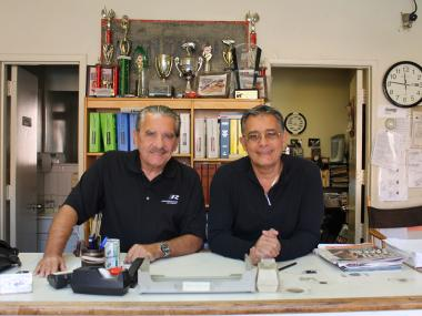 Picture Cars East owners Gino Lucci, 65, and Columbo Saggese, 62, pose for a photo in the shop's office.