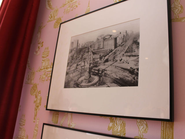 A historic photo of Columbus Circle is framed on the wall.