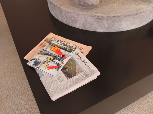 Bloomberg magazine, the Financial Times and the New York Times sit on the coffee table that surrounds the statue.