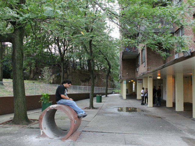 People hang out in the courtyard outside the entrance to Robert Fulton Terrace. Tenants said that rats often scurry from the direction of the construction site, down the hill (left) and onto the courtyard.