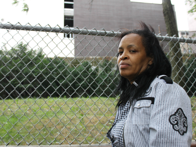 Linda Kemp, the tenant association president at Robert Fulton, stands at a fence separating the apartment building and a small hill below the construction site.
