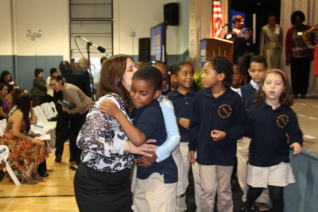 A student gets a hug from his teacher after performing during a welcoming at Teachers College Community School.