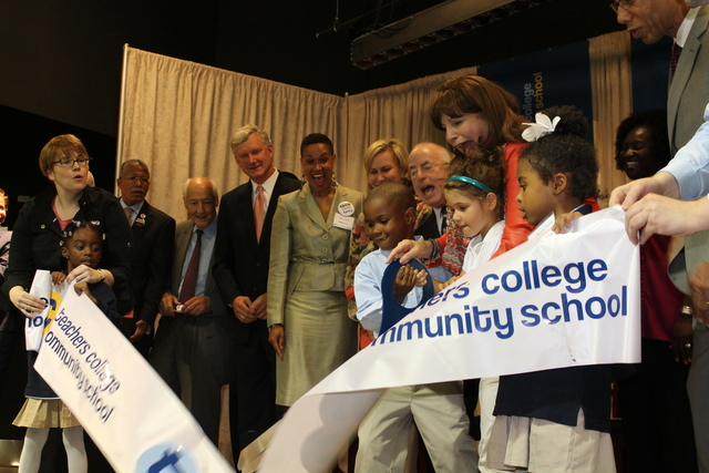 Students at Teachers College Community School cut a ceremonial ribbon with officials.