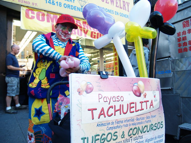 A local clown makes balloon animals at the Viva La Comida! festival in Jackson Heights.