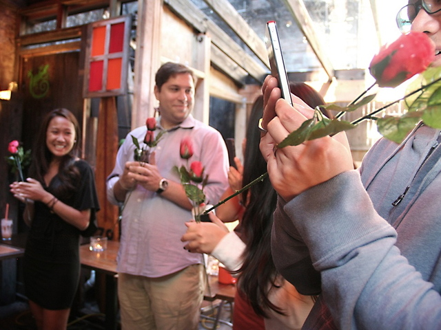 Family and friends wait with roses to greet the newly engaged couple.