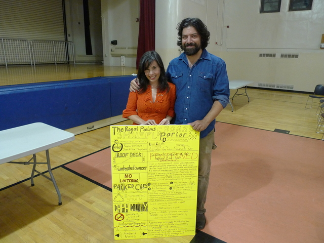 Ashley Albert and Jonathan Schnapp, co-owners of Royal Palms Shuffleboard Club in Gowanus, with a handmade poster they brought to Community Board 6 listing off concessions they've made in response to community concerns.